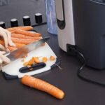 woman cutting carrots into pieces before blending