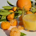 half full glass of orange juice and peeled and nonpeeled oranges on the side